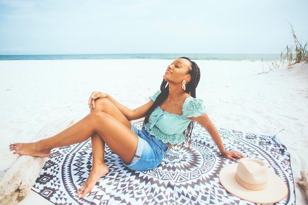 Woman at the beach sitting on Tesalate Beach Towel