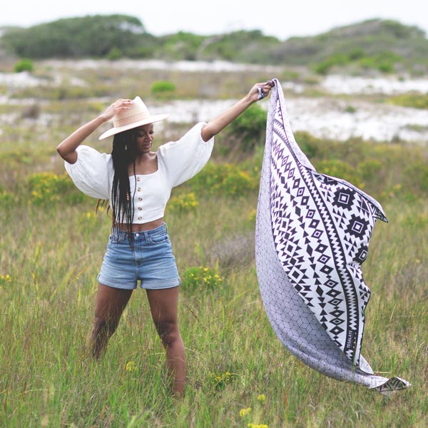 Model holding up the sand-free beach towel